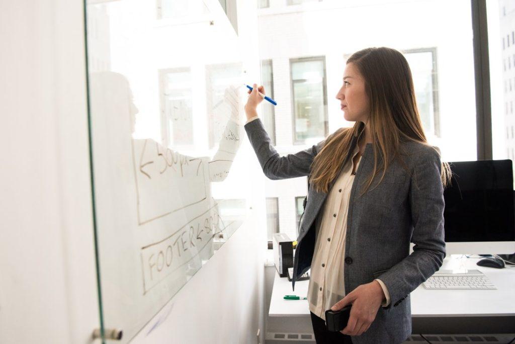 tablica suchościeralna i kobieta w biurze